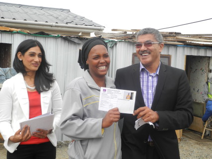 Cllr Derrick America (right) hands over ID card to community leader Verona Joseph (centre) with Salisha Lauton (left, Habitat for Humanity SA)