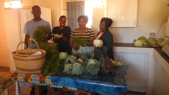 In holiday spirit, Umpheki Noks celebrates with the SA SDI Alliance and Masi Pink House staff at the Masi Soup Kitchen after the harvest of vegetables for christmas dishes of imifino (greens), seshebo (stew) and umngqusho (mash)