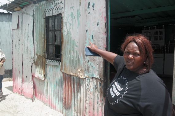ISN Community Leader Thamara Hela points to a structure that largely withstood the fire