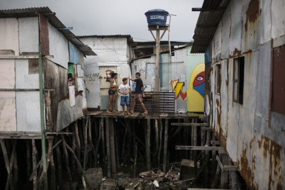 "In this Jan. 29, 2016 photo, Tainara Lourenco, who's five months pregnant, stands outside her stilt home that stands over polluted water in a slum in Recife, Brazil. Lourenco became pregnant at a scary moment — the dawn of an extraordinary Zika outbreak, as authorities came to suspect that the virus was causing an alarming spike in a rare birth defect called microcephaly. ""If you have to get sick you will get sick,"" she said. ""It's everywhere."" (AP Photo/Felipe Dana)"